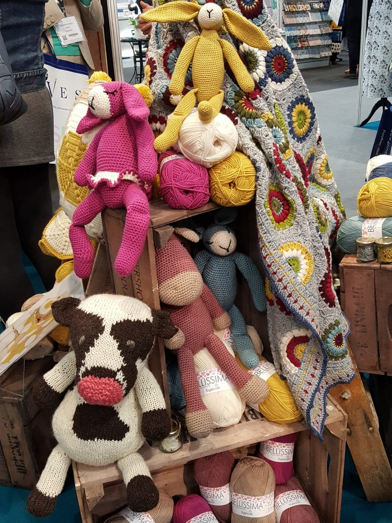 Prudence the prototype cow with crochet animals on the Stylecraft stall at CHSI Stitches 2019