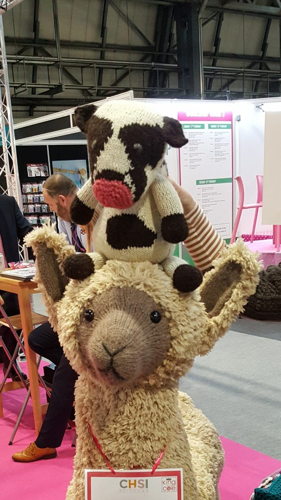 Prudence the prototype cow riding a giant knitted alpaca on the King Cole stall at CHSI Stitches 2019