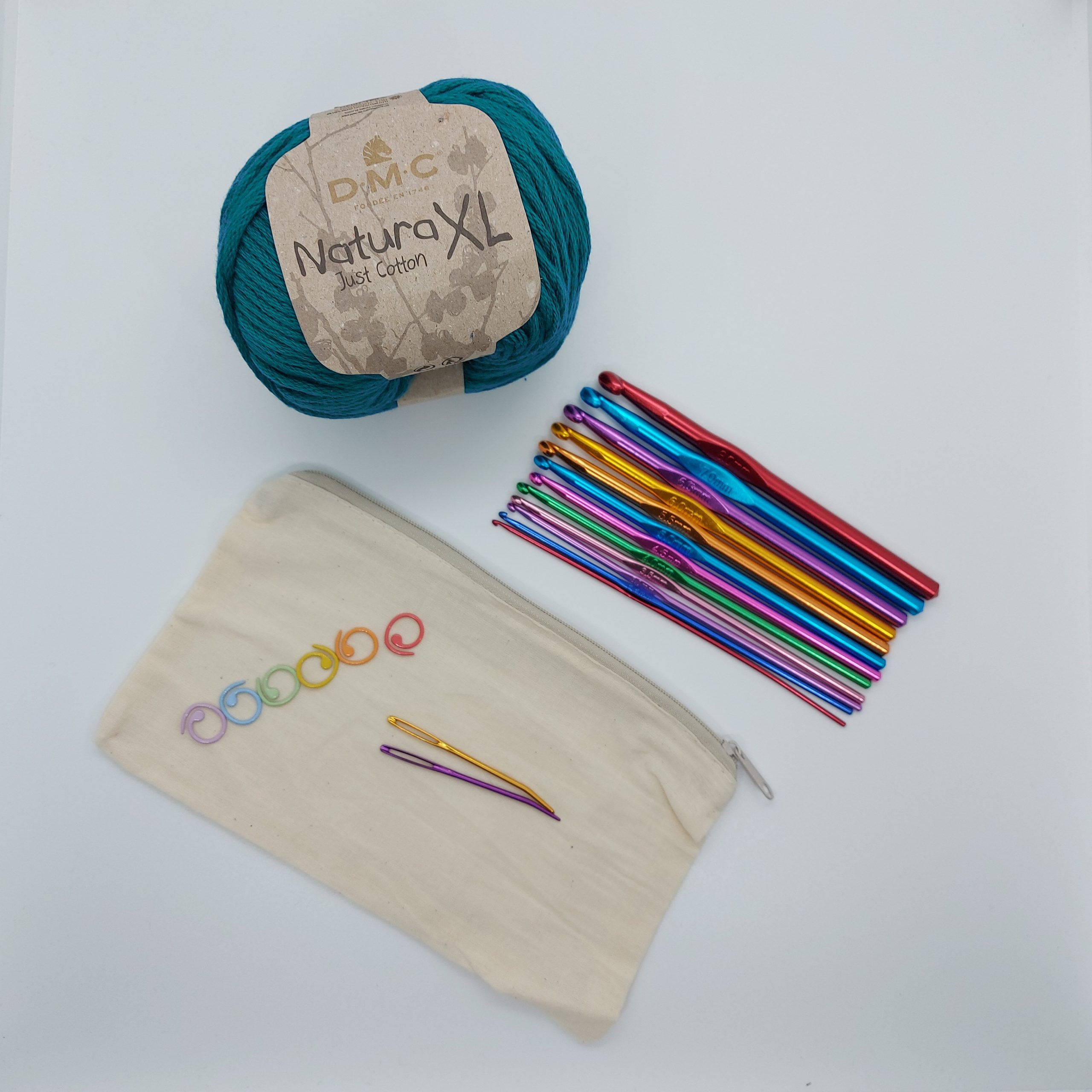 Crochet kit made of a set of hooks, a ball of yarn, bendy needles and stitch markers, with a zipped fabric pouch